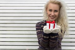 Härlig blond flicka som ger en gåva Arkivbild