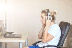 Härlig blond flicka som hemma lyssnar till musik på hörlurar arkivfoto