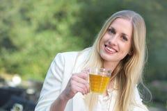 Härlig blond flicka som kopplar av med en kopp av Tea Royaltyfria Foton