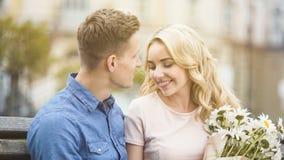 Härlig blond flicka som ler till den älskade mannen som rymmer den trevliga gruppen av blommor Royaltyfri Foto