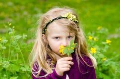 Härlig blond flicka som luktar blommor Royaltyfria Bilder