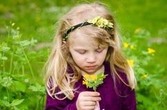 Härlig blond flicka som luktar blommor Arkivbild