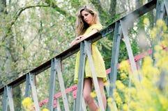 Härlig blond flicka som plattforer i en lantlig bro Royaltyfri Foto
