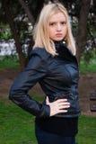 Härlig blond flicka som poserar i läderomslag Fotografering för Bildbyråer
