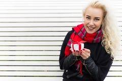 Härlig blond flicka som rymmer en gåva i deras händer kopiera avstånd Royaltyfria Foton