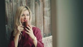 Härlig blond flicka som ser fönstret med en kopp kaffe i hans händer lager videofilmer