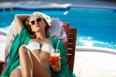 Härlig blond flicka som solbadar och att dricka coctailen som ligger nära simbassäng Arkivbilder
