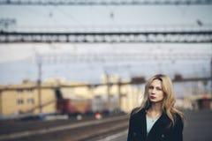 Härlig blond flicka som väntar på drevet på stationen romantiker delikat blick Arkivbilder