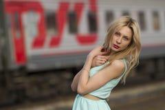 Härlig blond flicka som väntar på drevet på stationen romantiker delikat blick Fotografering för Bildbyråer