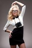 Blond flicka med kameran som ha på sig glasögon Arkivfoto