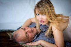 Härlig Blond-Haired kvinna i sexig damunderkläder som kramar hennes höga make som ligger i säng Par med ålderskillnad arkivfoto