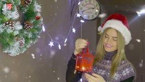 Härlig blond julflicka med den röda lyktan på bakgrund av julpynt stock video
