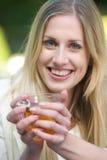 Härlig blond kopp för flickaHoldingTea arkivfoton