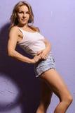 Härlig blond kvinna för modemodell i T-tröja och kortslutningar arkivbild