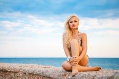 Härlig blond kvinna i baddräktsammanträde på havsbakgrundsbegrepp av ferie arkivfoton