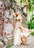 Härlig blond kvinna i beige lång klänning Arkivbilder