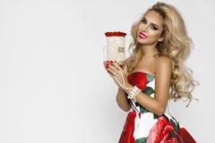 Härlig blond kvinna i en elegant aftonkappa med röda rosor som rymmer en valentin gåva, en flowerbox med blommor _ fotografering för bildbyråer