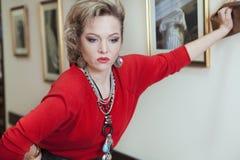 Härlig blond kvinna i en röd tröja Arkivbilder
