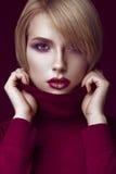 Härlig blond kvinna i en röd tröja med ljus makeup och mörka kanter Härlig le flicka royaltyfri bild