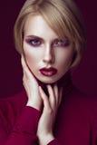 Härlig blond kvinna i en röd tröja med ljus makeup och mörka kanter Härlig le flicka fotografering för bildbyråer
