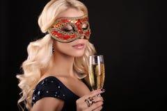 Härlig blond kvinna i karnevalmaskering, med exponeringsglas av champagne Arkivfoton