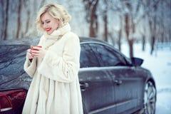 Härlig blond kvinna i lyxigt vitt pälslag som dricker varmt kaffe på snöig vinterdag Arkivfoto