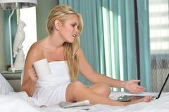 Härlig blond kvinna i säng - bärbar datordator Arkivfoto