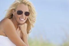 Härlig blond kvinna i solglasögon på stranden Arkivfoto