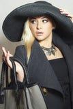 Härlig blond kvinna i svart hatt Trendig dam i överrock Elegansskönhetflicka med handväskan Shoppinghöst Arkivbild