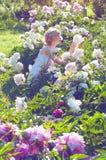 Härlig blond kvinna i vita sundress som sitter på gräsnen fotografering för bildbyråer