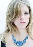 Härlig blond kvinna med den blåa halsbandet Arkivfoton
