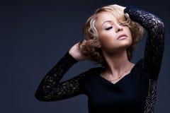 Härlig blond kvinna med den eleganta svart klänningen royaltyfria bilder