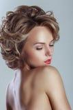 Härlig blond kvinna med den lockiga frisyren royaltyfri fotografi
