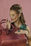 Härlig blond kvinna med den rosa handväskan Royaltyfri Foto