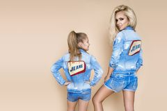 Härlig blond kvinna med hennes dotter i ett grov bomullstvillomslag och kortslutningar Modemodeller, i att bekläda för jeans Fotografering för Bildbyråer