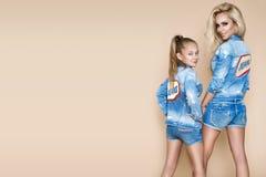 Härlig blond kvinna med hennes dotter i ett grov bomullstvillomslag och kortslutningar Modemodeller, i att bekläda för jeans Royaltyfria Foton