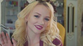 Härlig blond kvinna med lång lockigt hår- och stilmakeup som poserar på kameran stock video