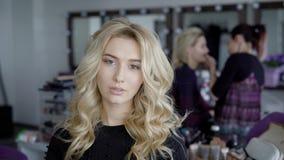 Härlig blond kvinna med lång lockigt hår- och stilmakeup som poserar seductively på kameran Modell med att charma ögon stock video
