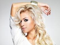 Härlig blond kvinna med långt lockigt hår Royaltyfri Fotografi