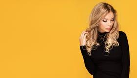 Härlig blond kvinna med långt lockigt hår arkivbild