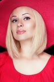Härlig blond kvinna med makeup, sinnliga kanter som bär i rött Royaltyfri Bild