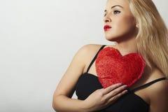 Härlig blond kvinna med röd hjärta. Skönhetflicka. Visa förälskelsesymbolet. Valentin Day.Passion Royaltyfria Bilder