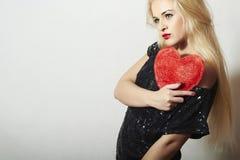Härlig blond kvinna med röd hjärta. Skönhetflicka. Visa förälskelsesymbolet. Valentin Day.Passion Royaltyfri Foto