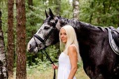 Härlig blond kvinna och grå färghäst i skog Royaltyfri Foto