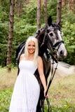 Härlig blond kvinna och grå färghäst i skog Royaltyfri Fotografi