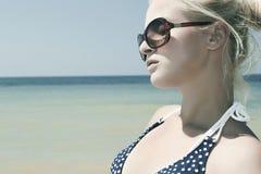 Härlig blond kvinna på stranden i solglasögon Arkivfoton