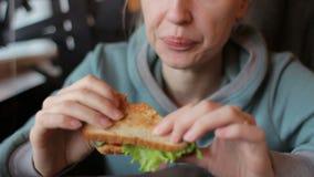 Härlig blond kvinna som äter den vegetariska smörgåsen med nya grönsaker i kafé lager videofilmer