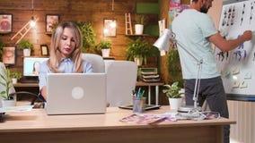 Härlig blond kvinna som arbetar på hennes dator i en yrkesmässig idérik arbetsplats arkivfilmer