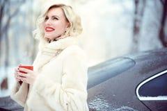 Härlig blond kvinna som bär det lyxiga vita pälslaget som dricker varmt kaffe på snöig dag och att skratta för vinter Arkivbild