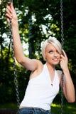 Härlig blond kvinna som dagdrömmer på en gunga royaltyfri foto